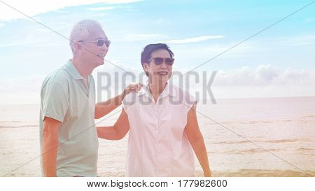 Asian Senior Couple Walking Together On Beach By The Sea