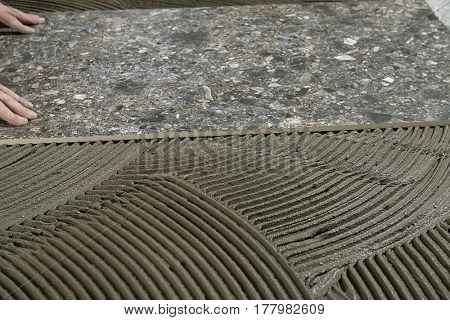Hand of a construction worker installing ceramic tile.