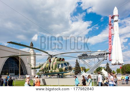 MOSCOW - MAY 8 2016: People near the military transport helicopter Mil Mi-8T and Vostok rocket in VDNKh park. It was build in soviet times as an Exhibition of Achievements of National Economy.