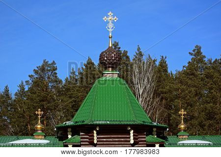 The roof of wooden Russian Orthodox Christian Gate Church in Ganina Yama Monastery against the forest and sky Spring, Ekaterinburg, Russia.