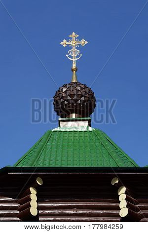 The dome with cross of Russian Orthodox Christian Gate Church in Ganina Yama Monastery against the sky, Ekaterinburg, Russia.