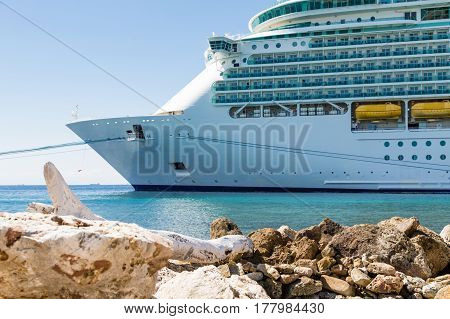 Luxury Cruise ship moored in harbor beyond rock seawall on Curacao