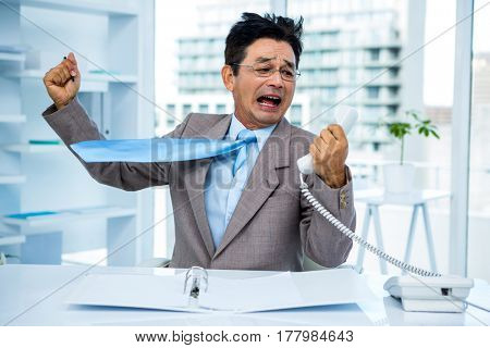 Businessman shouting as he holds out phone in office
