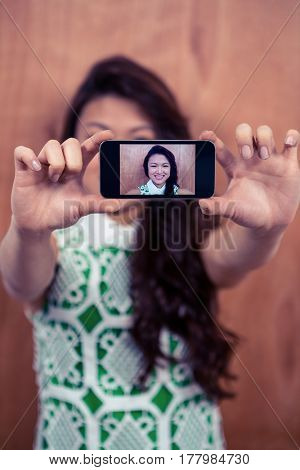 Smiling Asian woman taking selfie against wooden wall