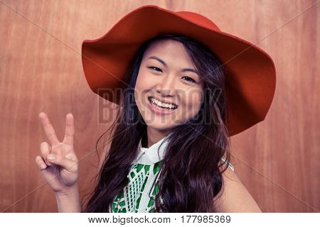 Smiling Asian woman doing peace sign with hand against wooden wall