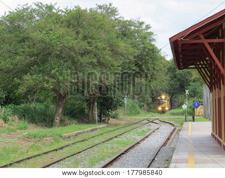 Freight train arriving at a small empty railway station, near the intersection, in sunny day, with lighted headlights, in the field in Brazil