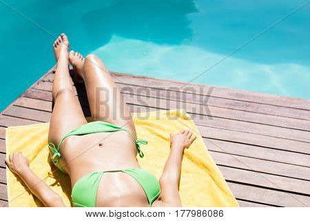 Fit woman lying on towel by the pool