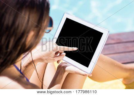 Over shoulder view of brunette using tablet poolside