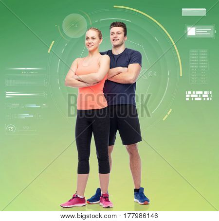 sport, fitness, technology and people concept - happy sportive man and woman over green background