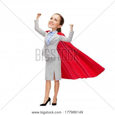 business, success, achievement and people concept - young smiling businesswoman in red superhero cape holding raised fists, funny character with big head
