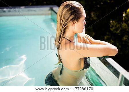 Beautiful blonde in the pool looking the landscape