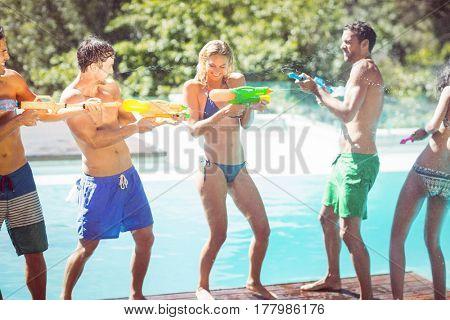 Happy friends doing water gun battle poolside