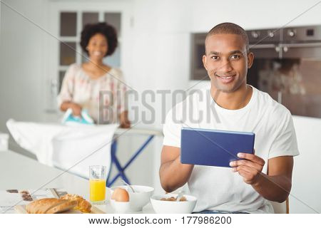 Young man using tablet in kitchen and her girlfriend ironing