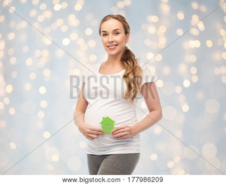 pregnancy, ecology, people and housing concept - happy pregnant woman with green house over holidays lights background