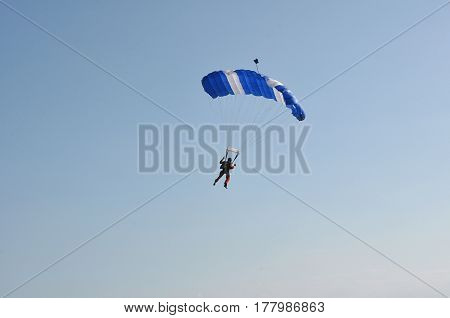 young man jumping with a parachute in the sky