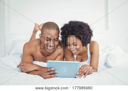 Smiling couple using tablet on bed at home