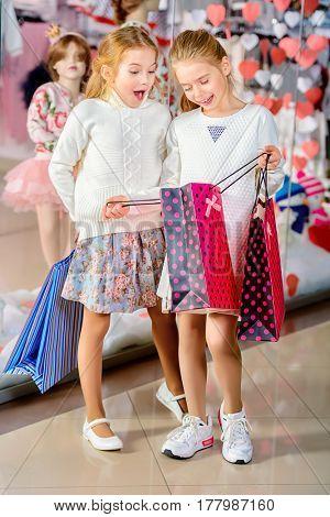 Two cute little girls go shopping. Kid's fashion. Modern children. Seasonal sale, shopping.