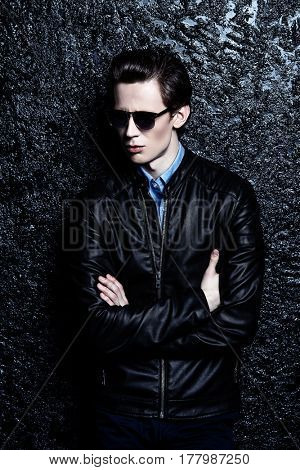Modern young man in sunglasses and leather jacket over black background. Men's beauty, fashion.