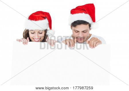 Happy couple with santa hat holding a poster on white background