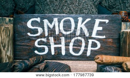 Smokers goods on wood stands. Wooden signboard with text 'Smoke shop'. Close-up view