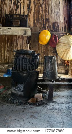 Black old kettle on sitting on small old firewood stove filled with charcoal inside wooden hut in the afternoon.