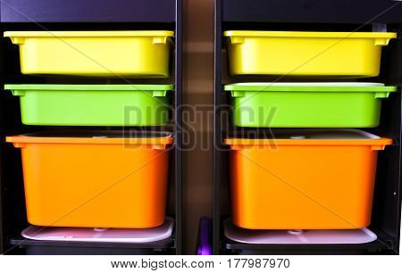 Two Rows Of Yellow, Green And Orange Plastic Boxes In Black Shelf