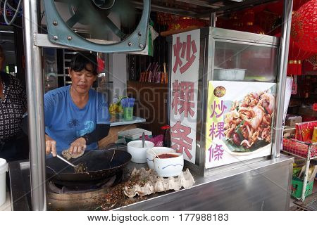 Women Cooks Kway Teow Noodles At The Street Food Night Market In Penang