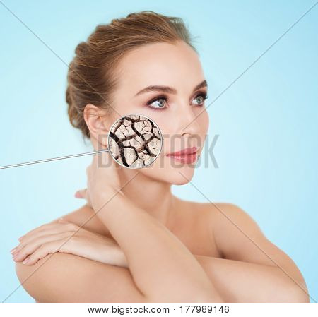 beauty, people and skin care concept - beautiful young woman face with dehydrated cracked dry skin over blue background