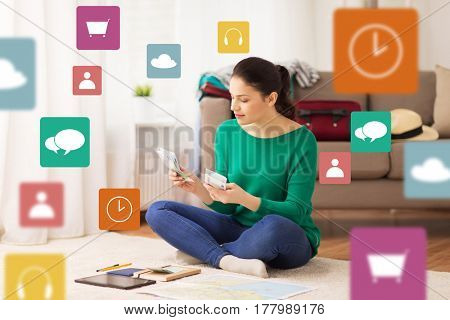 tourism, travel, finances and people concept - happy young woman with money, tablet pc computer and map at home over multimedia icons