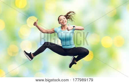 sport, fitness, motion and people concept - happy smiling young woman jumping in air and showing thumbs up over summer green lights background