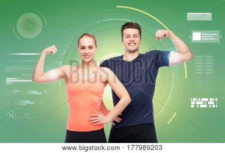sport, fitness, power, technology and people concept - happy sportive man and woman showing biceps over green background