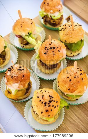 Appetizer sliders on wooden serving tray