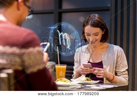 technology, astrology, horoscope and people concept - happy couple or friends with smartphones and scorpio zodiac sign having dinner at restaurant