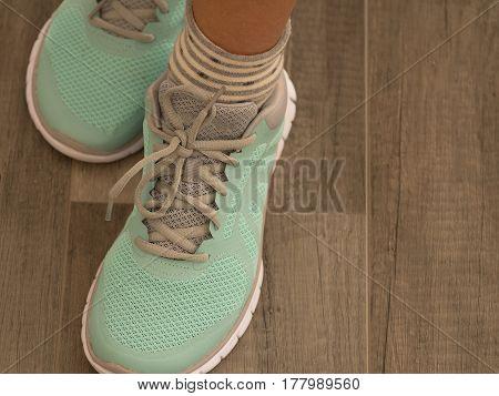 Light Green Sport Shoes On Wooden Floor