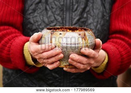 old woman with old iron pot with porridge in her hands. traditional russian food.