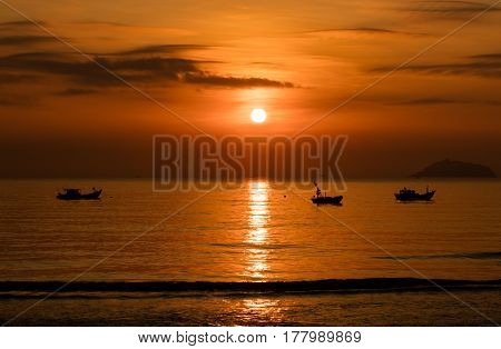 A fiery orange sunrise sky looking out over the south China sea in Vung Lam Bay Vietnam. With a fishing boats in silhouette.