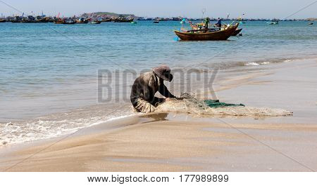 Fisherman sitting on a white sand beach shore in the morning sun fixing his net with his hands to catch more fish Vietnam.