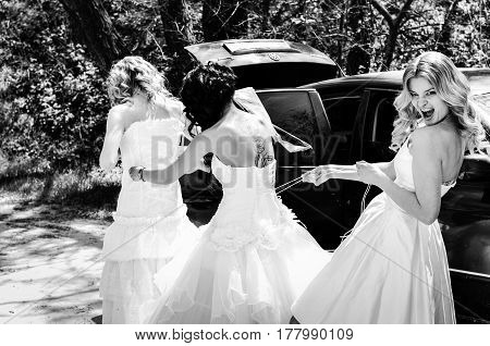 Three Stylish young smiling blonde bride with her bridesmaids in blue summer dress in the park on her happy wedding day.