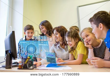 education, elementary school, learning, technology and people concept - group of kids with teacher looking to computer monitor in classroom over virtual screens projections