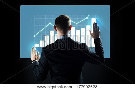 business, people, technology, cyberspace and statistics concept - businessman in suit working with diagram chart on virtual screen over black background