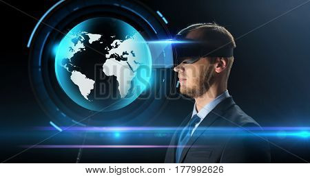 technology, people, cyberspace, mass media and augmented reality concept - young businessman with virtual headset or 3d glasses and earth hologram over black background