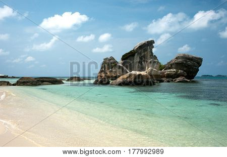 Natural rock formation in the sea and on a white sand beach in Belitung Island in the afternoon Indonesia.