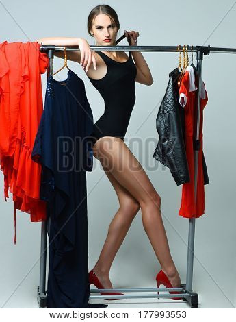 Pretty girl or sexy woman slim fashion model in sexi black bodysuit posing on high heel shoes with red dress and leather jacket on hangers at clothes rack wardrobe on grey background