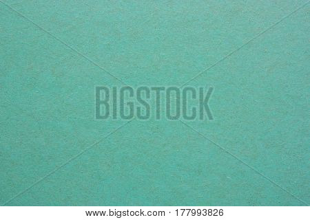 A blank sheet of paper or plywood green color. Rough surface of background. Concept of recycling raw materials. Natural paper background texture for your design. Rustic, vintage style. Horizontal.