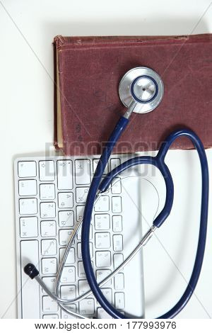 A medical stethoscope near a laptop on table on white.