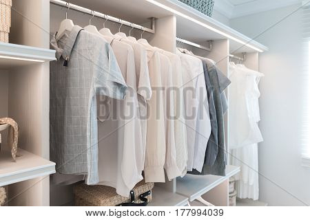 Modern interior wardrobe with shirt and dress in shelf.