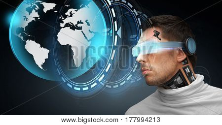 people, technology, future and progress - man with 3d glasses and microchip implant or sensors with virtual earth projection over dark background