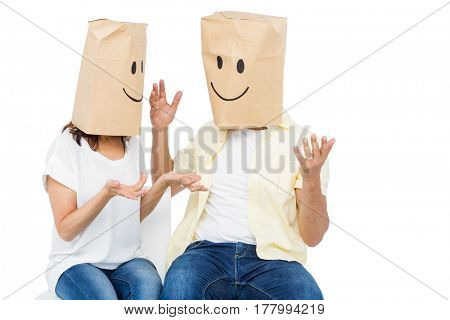 Couple covering their faces with paper bag over white background