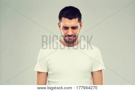 emotion, sadness and people concept - unhappy young man over gray background