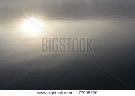 A reflection of the sun in the water.